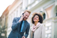Two business people in an informal conversation. In front of a business building, men using phone Stock Photos
