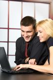 Two business people on laptop. Two happy smiling young business people on laptop, working, chatting, playing or searching in internet royalty free stock image