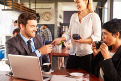 Two business people with laptop paying in a coffee shop Royalty Free Stock Photo