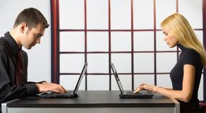 Two business people on laptops. Young attractive smiling couple or business people on laptops working, chatting Royalty Free Stock Photos