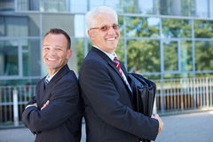Two business people leaning on each Stock Images