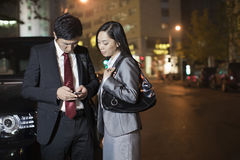 Two Business People Looking At Cell Phone Stock Photography