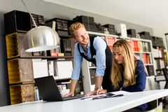 Two business people are looking at the laptop screen and talking. In office Royalty Free Stock Photos