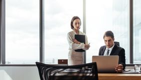 Two business people looking at laptop. While working in the office. Businessman sitting at his desk with female coworker standing by Royalty Free Stock Image