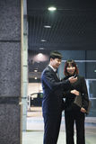 Two business people looking at phone in a parking garage, Beijing Royalty Free Stock Images