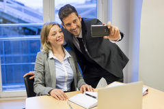 Two business people making a Selfie in the office Stock Photos