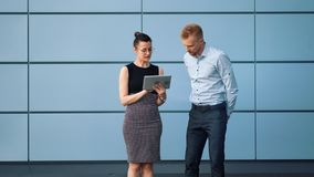 Two business people man and woman greeting each other shaking hands outdoor using tablet pc. Two business people man and woman greeting each other shaking hands stock footage