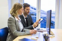 Two business people in a office, working on computer and tablet Stock Images
