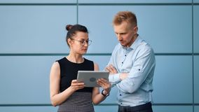 Two business people in official outfit discussing working using tablet pc outdoor medium shot. Busy colleague businesswoman and businessman having informal stock footage