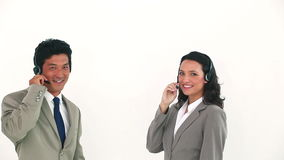 Two business people posing with headsets. Against a white background stock video