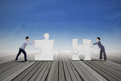 Two business people put two puzzles Royalty Free Stock Images