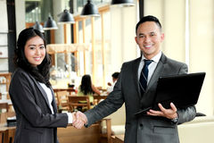Two business people shake hands after have a deal with their pro Stock Photography