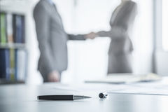 Two business people shaking hands in the background, pen lying on the table in the foreground Stock Images