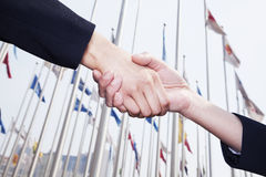 Two business people shaking hands in Beijing, flags flying in the background Royalty Free Stock Photography