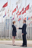 Two business people shaking hands in Beijing, flags flying in the background Stock Photos