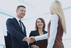 Two business people shaking hands with each other in the office Stock Photography