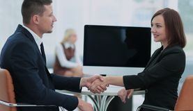 Two business people shaking hands and looking at each other with Royalty Free Stock Images