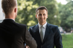 Two Business People Shaking Hands Outdoors Royalty Free Stock Image
