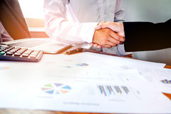 two business people shaking hands while sitting at the working p stock photo