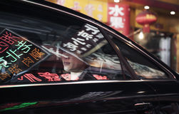 Two business people sitting in the back of a car driving through the city at night, reflections of store signs on the car Stock Photo