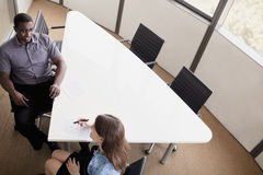 Two business people sitting at a conference table and discussing during a business meeting stock photos