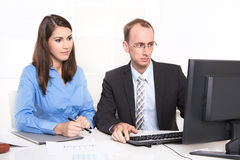 Two business people sitting at desk. Royalty Free Stock Images