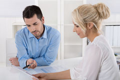 Two business people sitting in the office working in a team look. Ing at balance sheet or assessment report stock images