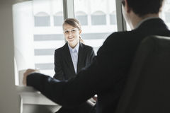 Two business people sitting, smiling and looking at each other during a business meeting Stock Image