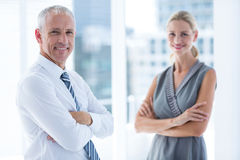 Two business people smiling at the camera in the office Royalty Free Stock Photos