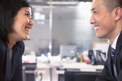 Two business people smiling and laughing face to face royalty free stock photography