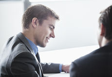 Two business people smiling and looking down at a business meeting Royalty Free Stock Image