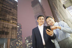 two business people smiling and looking at the phone Royalty Free Stock Photo