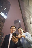 Two business people smiling and looking at the phone, pointing, outdoors at night, low angle view Royalty Free Stock Photography