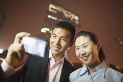 Two business people smiling and taking a picture of themselves with the phone at night Stock Images