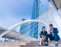 Two business people standing and discussing urban city building background. stock photos