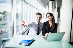 Two business people taking a Selfie in the office. Work and selfie. Two business people taking a Selfie in the office Stock Images
