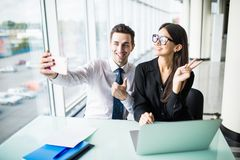 Two business people taking a Selfie in the office. Work and selfie. Two business people taking a Selfie in the office Stock Photo