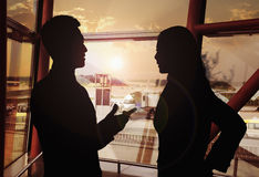 Two business people talking in the airport, Silhouette Stock Photography