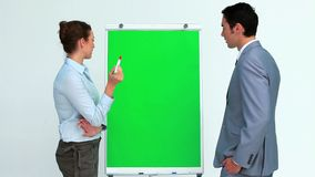 Two business people talking in front of a board. In studio stock footage