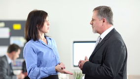 Two business people talking in office. Two business people talking and chatting in an office (Full HD stock video footage