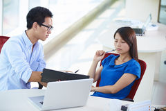 Two business people talking in the office. Two young asian business people working in the office Royalty Free Stock Images