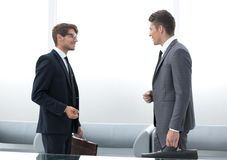 Two business people talking standing in the office royalty free stock photo
