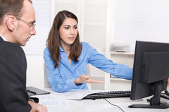 Two business people talking together at desk - adviser and custo Royalty Free Stock Images