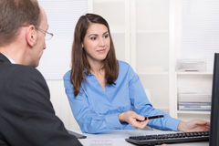 Two business people talking together at desk - adviser and custo Stock Image