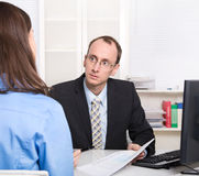 Two business people talking together at desk - adviser and custo Royalty Free Stock Photo