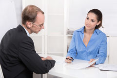 Two business people talking together at desk - adviser and custo Royalty Free Stock Photography
