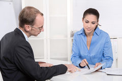 Two business people talking together at desk - adviser and custo Stock Photos