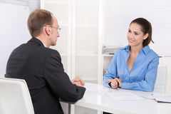 Two business people talking together at desk - adviser and custo Royalty Free Stock Image