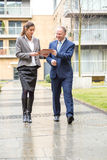 Two business people walking and discussing Stock Photos
