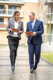 Two business people walking and discussing. Outside the office Royalty Free Stock Photos